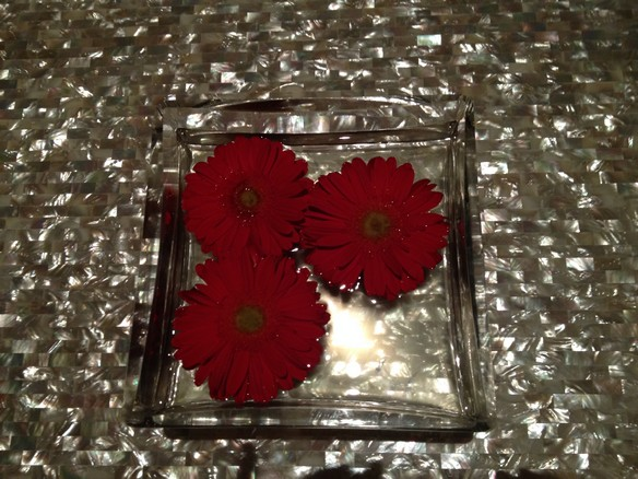 Red flowers in a glass dish on a marble table